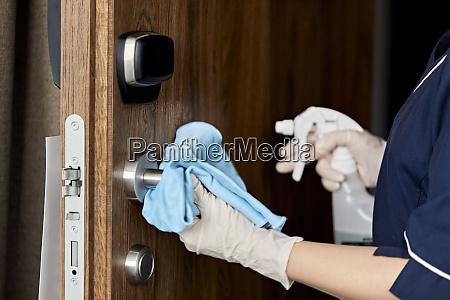 close up of chambermaid wiping doorknob