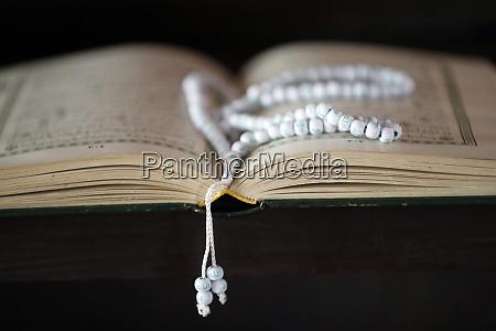 open quran and islamic prayer beads