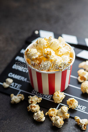 sweet popcorn in cup and clappeboard