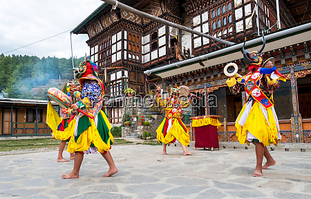 bhutanese people performing the masked cham