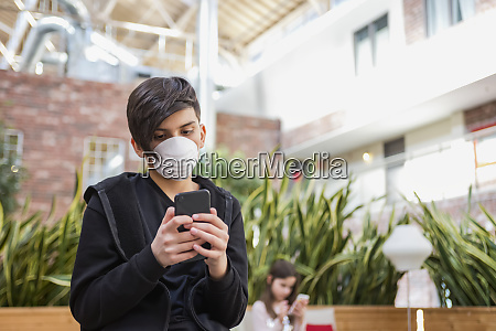 boy with smart phone wearing protective