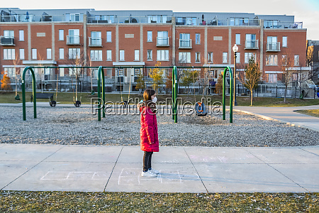 young girl stands at a playground