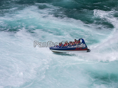 tourists take a speedboat through the