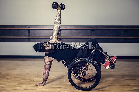 a paraplegic man popping a wheelie