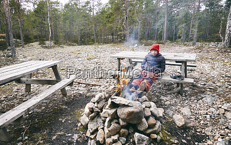 boy sitting on picnic bench next