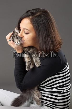 studio shot of woman hugging grey