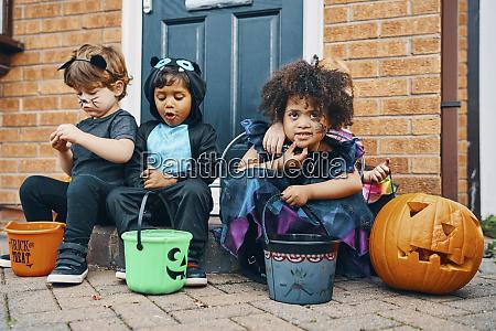 three children dressed for halloween sitting