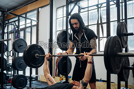 one man bench pressing a weight
