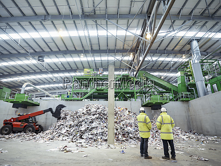 workers inspecting waste paper in waste