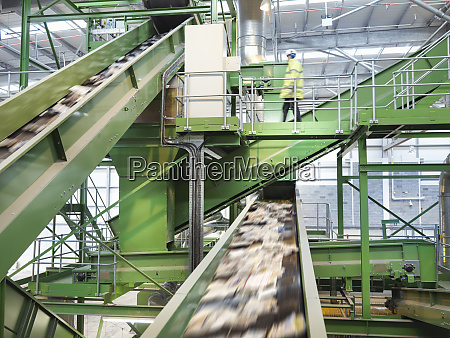 worker checking conveyor belts with waste
