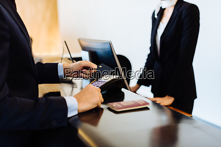 businessman making contactless payment at hotel