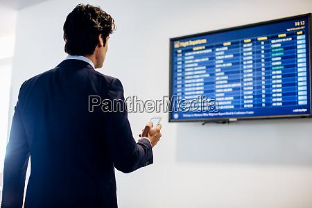 businessman checking departure board