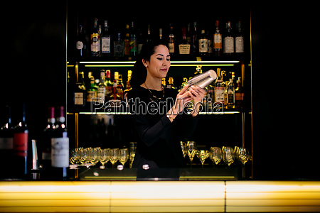 young barmaid preparing cocktail in boutique