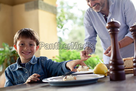 boy at table whilst father prepares
