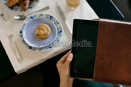 womans hand removing digital tablet from