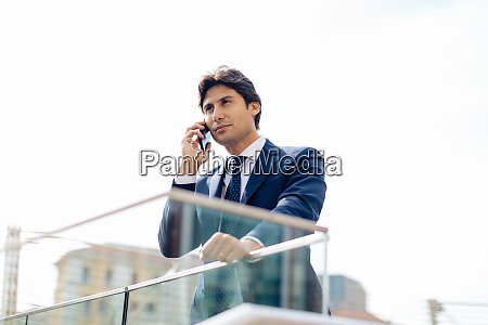 businessman using smartphone on terrace