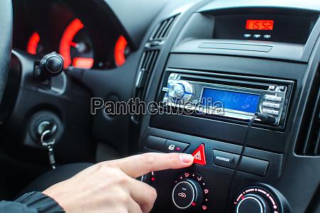 detail on car dashboard man finger