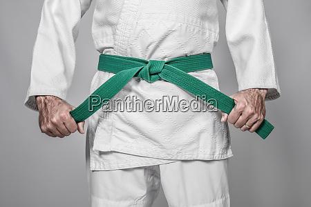martial arts practitioner tightening his belt