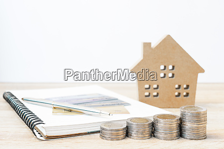 house model and notepad with coins