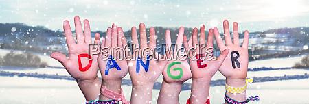 children hands building word danger snowy