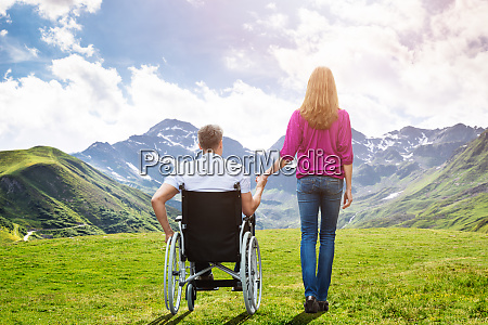 walking with disabled patient caring wife