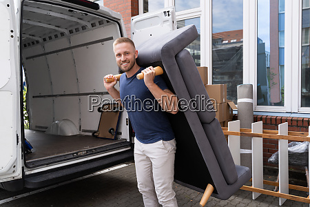 man lifting sofa or couch furniture