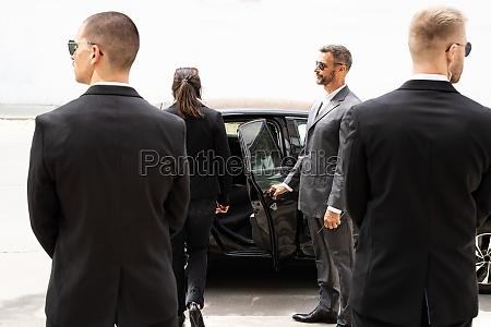 bodyguards protecting businesswoman opening car door