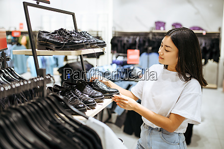 young woman choosing shoes in clothing