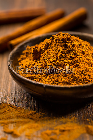 cinnamon powder in wooden bowl with