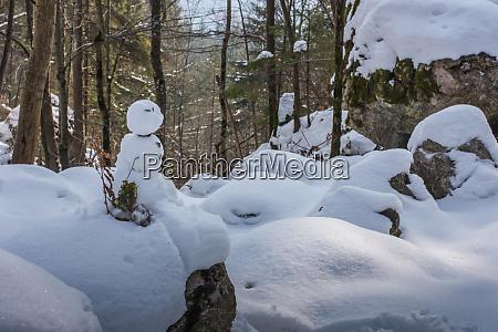 kleiner schneemann im schnee und gebirge