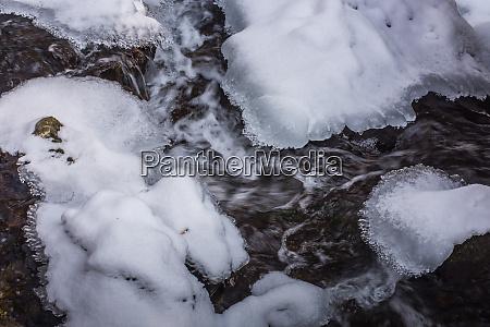 wirbelndes wasser mit eis und schnee