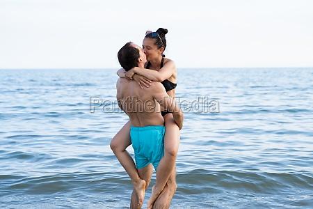 lifting woman at beach at sea