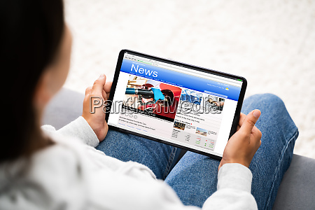 watching news on tablet computer screen