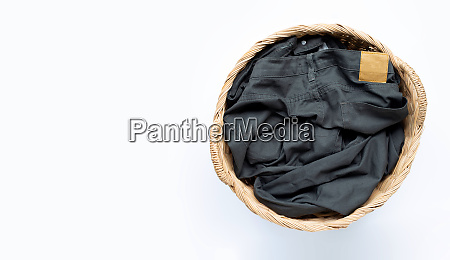 trousers in laundry basket on white