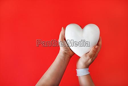 white heart in hands