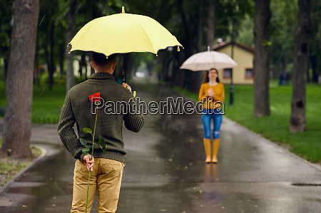 love couple with umbrellas and rose