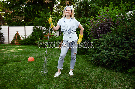 smiling woman with rake works in