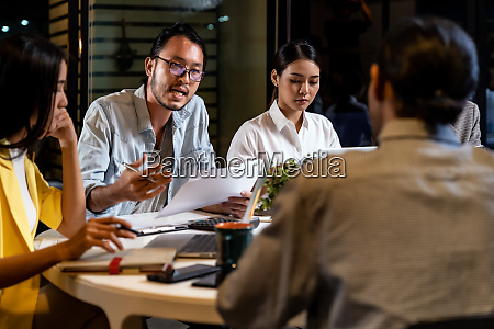 working late interracial asian business team