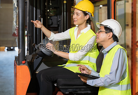 asian warehouse forklift worker discuss to
