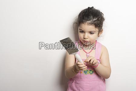 little girl holding a large paintbrush