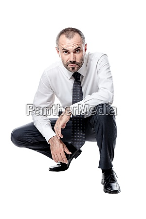 businessman crouching isolated on white