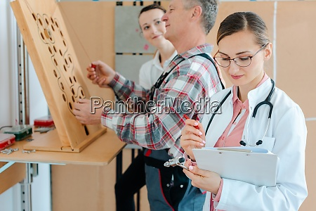 doctor writing down results from occupational