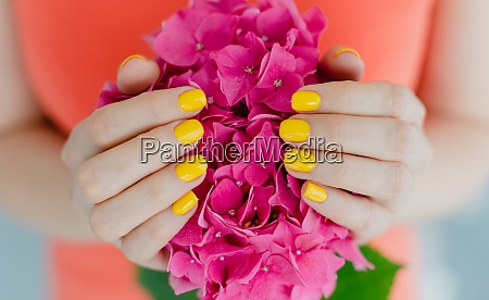 women with manicured nails in yellow
