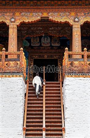 bhutanese man in traditional dress climbing