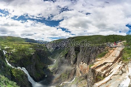 hikers admiring voringsfossen waterfall from the