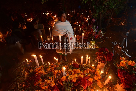 zapotec woman holding candle among graves
