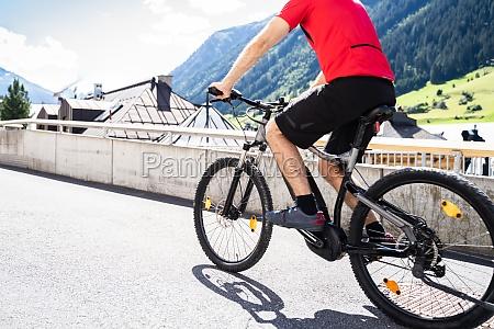 man riding e bike bicycle in