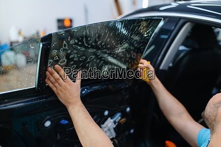 worker installs wetted car tinting tuning