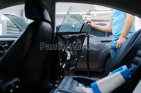 worker prepares car for tinting tuning