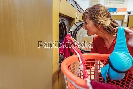 woman loding laundry in washing machine